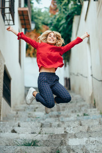Happy young blond woman standing on beautiful steps in the stree