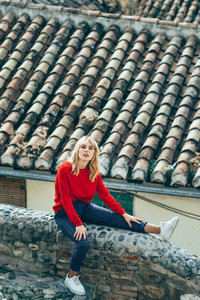 Young blond woman sitting near beautiful roofs of charming old houses