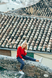 Happy young blond woman sitting near beautiful roofs of charming old houses
