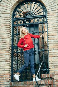 Happy young blond woman next to urban door