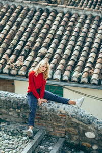 Young blond woman sitting near beautiful roofs of charming old h