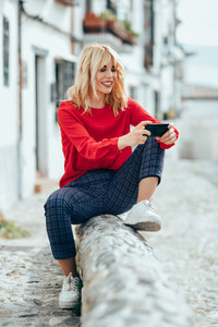 Young blond woman sitting on urban background using smart phone