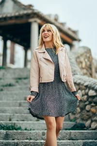 Smiling blonde girl wearing dress dancing outdoors