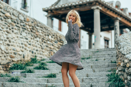 Smiling blonde girl wearing dress dancing outdoors