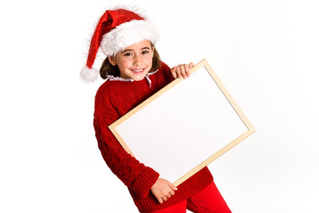 Little girl wearing santa hat holding blank board