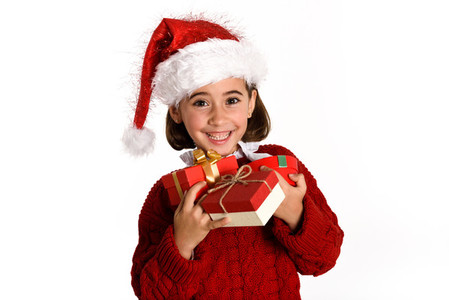 Little girl wearing santa hat carrying many gift boxes
