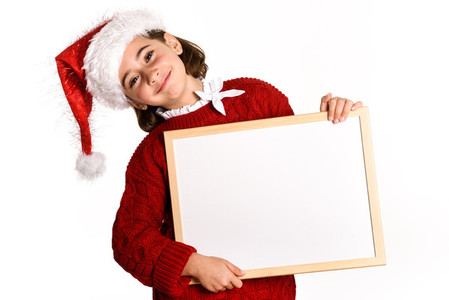 Little girl wearing santa hat holding blank board