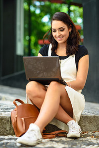 Student girl typing on laptop computer sitting on urban steps