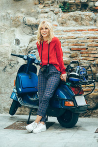 Young blond woman sitting on an old blue scooter wearing red clothes