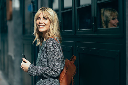 Attractive young caucasian woman looking at her smart phone outdoors