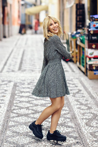 Funny young blonde woman standing on urban background