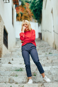 Happy young blond woman laughing on beautiful steps in the street