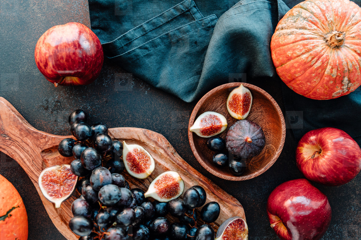 Top view of Autumn food still life with season fruits and vegetables like Bangalore blue grape  red apples  pumpkins and figs on a table