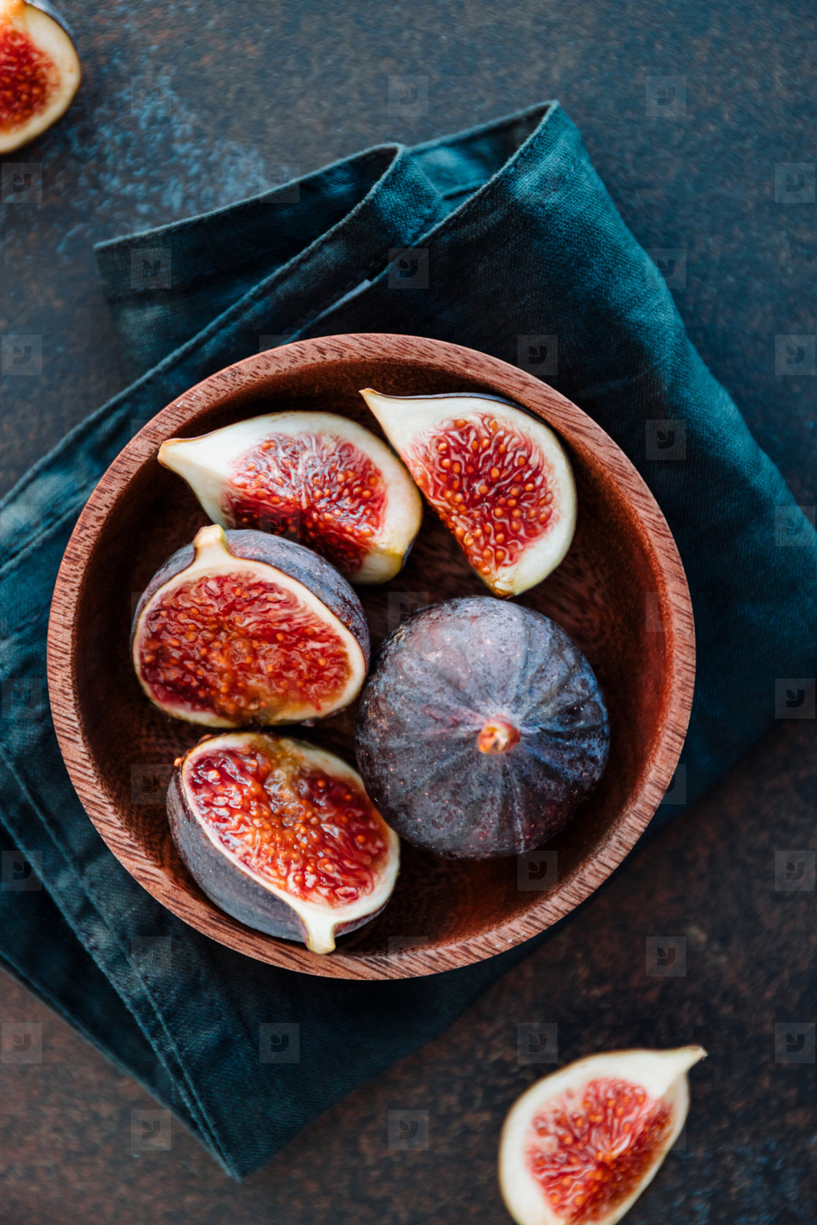 Top view of ripe quartes figs in a wooden small bowl on a table