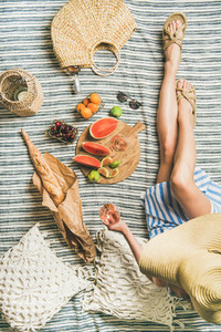 Picnic setting with woman in dress wine fruits and baguette