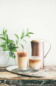 Iced coffee drink in tall glasses with milk  vertical composition