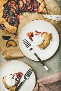 Flat lay of plum galetta sweet cake pieces with ice cream