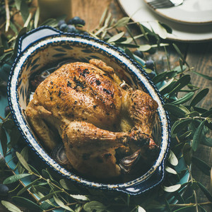 Whole roasted chicken decorated with olive tree branch square crop