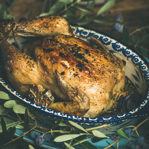 Whole roasted chicken with garlic over wooden background square crop