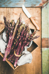 Fresh raw uncooked purple asparagus over rustic background selective focus