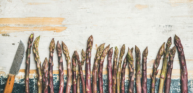 Fresh Raw purple asparagus over rustic wooden background  copy space