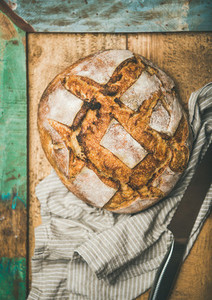 Flat lay of sourdough wheat bread over rustic background