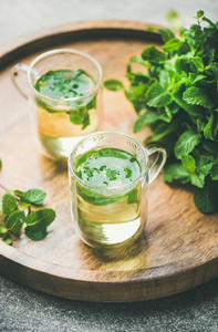 Hot herbal mint tea drink in glass mugs with leaves