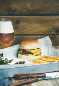 Classic burger dinner with french fries salad and beer