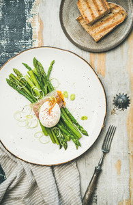 Flat lay of green asparagus  soft boiled egg   bacon and toasts