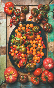 Flat  lay of fresh colorful tomatoes on plate vertical composition