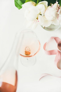 Rose wine in glass  pink ribbon  peony flowers on table