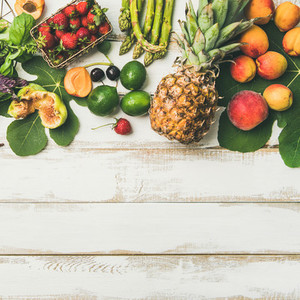 Seasonal fruit vegetables and greens over wooden background square crop