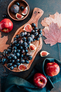 Top view of Autumn food flat lay with season fruits llike Bangalore blue grape red apples and figs on a table