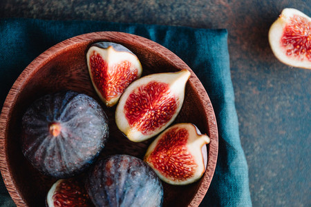 Top view of ripe figs in a wooden small bowl on a table