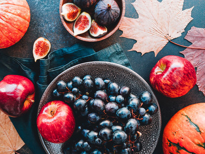 Top view of Autumn food flat lay with season fruits and vegetables like Bangalore blue grape  red apples  pumpkins and figs on a table