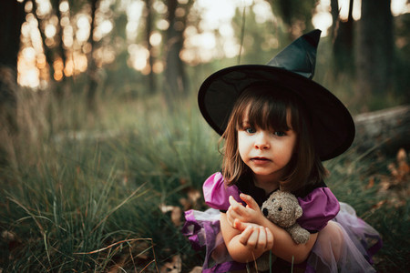 Smiling girl disguised as a witch in the woods during Halloween