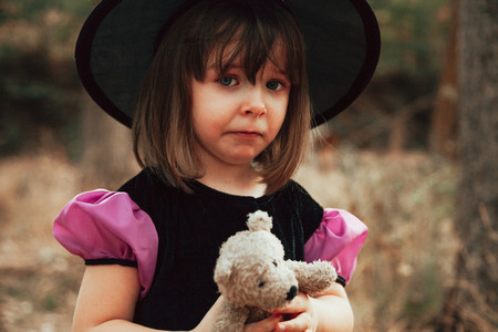 Sad girl disguised as a witch in the woods during Halloween