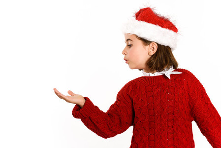 Adorable little girl wearing santa hat blowing to her hand