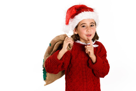 Adorable little girl wearing santa hat carrying gift bag