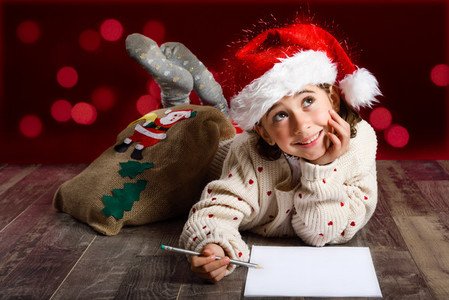 Adorable little girl wearing santa hat writing Santa letter