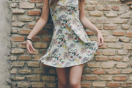 Sexy woman raising her dress on brick wall