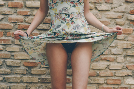Young woman showing her panties by raising her dress