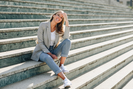 Beautiful young blonde woman smiling on urban steps