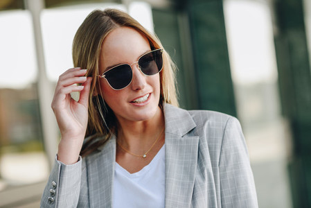 Beautiful young blonde woman with sunglasses in urban background