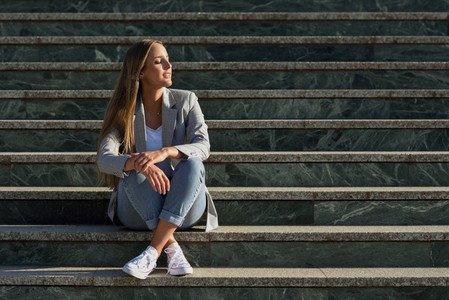Beautiful young caucasian woman with eyes closed sitting on step