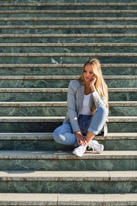 Thoughtful young blonde woman sitting on urban steps