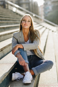Beautiful young blonde woman sitting on urban steps