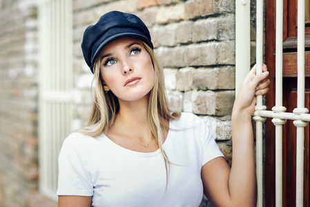 Young blonde woman wearing cap standing near a brick wall