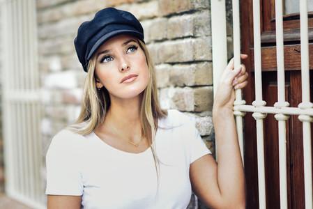 Young blonde woman wearing cap standing near a brick wall