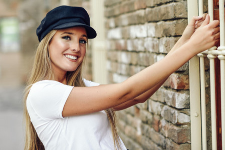 Young blonde woman wearing cap smiling near a brick wall